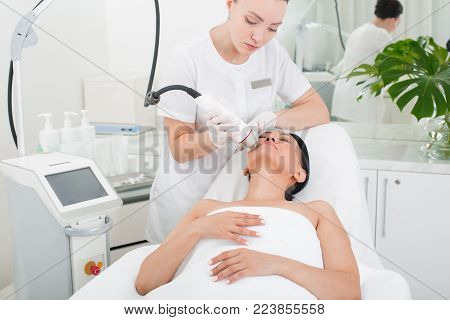 Tranquil mature lady relaxing in beauty salon. Woman is lying in a chair while specialist taking care of her skin by rejuvenating equipment