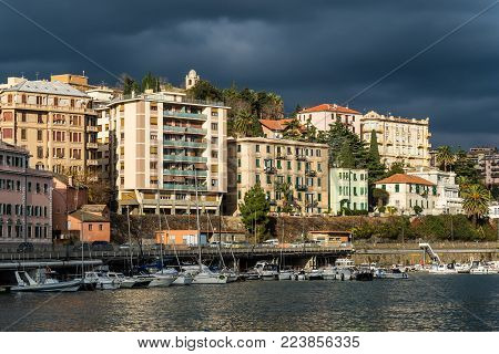 Savona, Italy - December 2, 2016: View of the Residential houses in the sun against the background of thunderclouds before the storm at the Ligurian sea port in Savona, Italy.