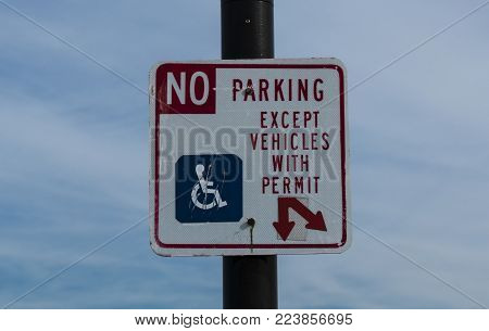 A sign dictating that there is No Parking except for vehicles with a hanicapped permit.
