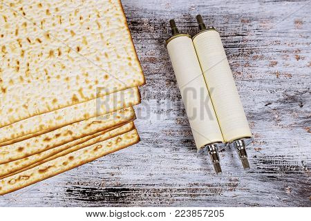 top view of passover background. matzoh jewish holiday bread and traditional Torah scroll during over wooden board