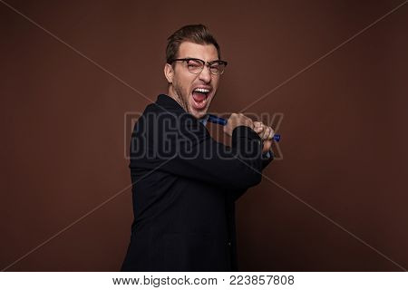 Portrait of screaming bearded man swinging sporting equipment. Aggression and safe concept. Isolated