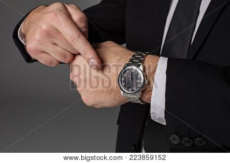 Close up male hand pointing on wristwatch. It situating on wrist. Availability concept