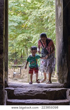 Sambor Prei Kuk, Cambodia - January 01, 2017: Mother and son entering in Prasat Yeay Poan anciente temple. The now ruined complex dates back to the Pre-Angkorian Chenla Kingdom