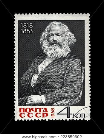 MOSCOW, USSR - CIRCA 1968: canceled postal stamp printed in the USSR shows Karl Marx, famous politician leader, Capital book author, circa 1968. Vintage stamp isolated on black background.