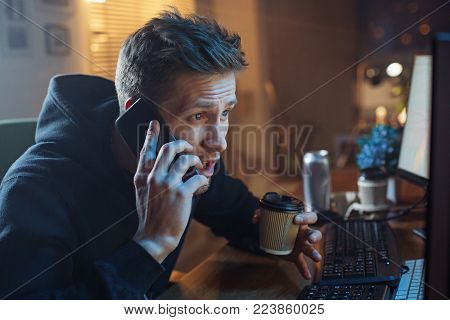 Portrait of serene bearded man telling by mobile while drinking mug of hot beverage. He having job with gadgets at home. Occupation and appliance concept