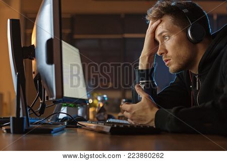 What is it. Side view surprised unshaven man watching at display of computer while drinking alcohol beverage. He hearing songs in headset. Profession and leisure concept