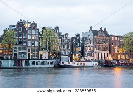 Amsterdam, Netherlands - April 21, 2017: View of typical Amsterdam houses along canal on cloudy sky. Sailboats have tours on Amsterdam canals.