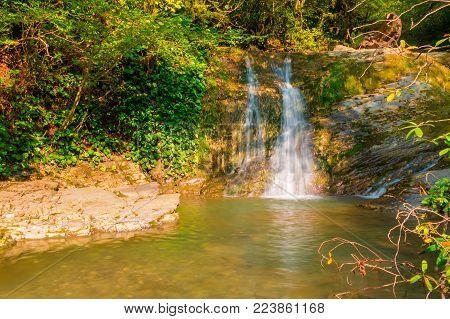The cascade waterfall of the mountain river Bezumenka in sunny autumn day, Sochi, Russia
