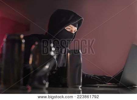 Low angle portrait of calm computer burglar working with gadget while situating at desk in room. Technology and steal concept