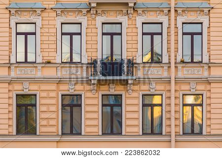 Several windows in a row and balcony on the facade of the urban historic building front view, Saint Petersburg, Russia