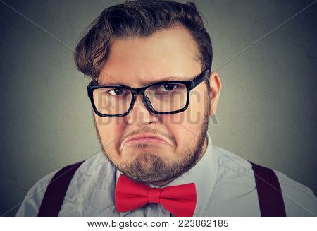 Headshot of chubby man in red bowtie and glasses looking at camera with expression of displeasure.