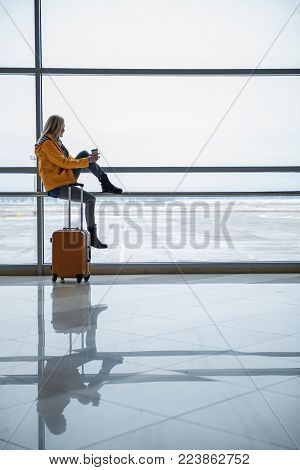Start of her travel. Full length of young woman with suitcase is looking through window while waiting for boarding at terminal lounge. She is sitting on handrail and drinking coffee. Copy space