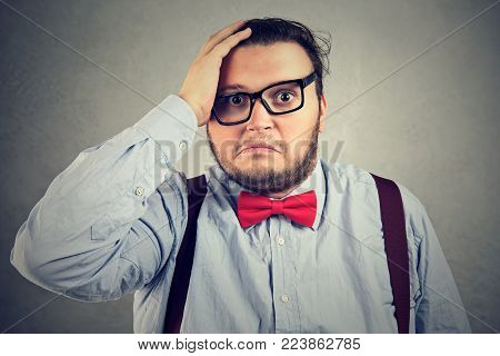 Chunky man looking desperately at camera on gray backdrop.