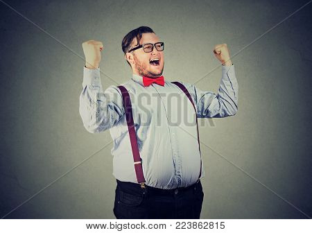 Chubby man in formal clothing holding hands up celebrating achievement.