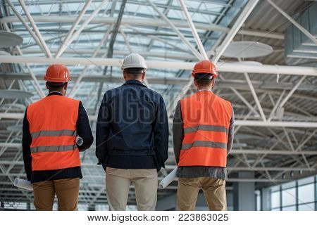 Low angle of qualified engineers in safety-helmets are standing at construction area. They are looking at their project while holding blueprints. Back view