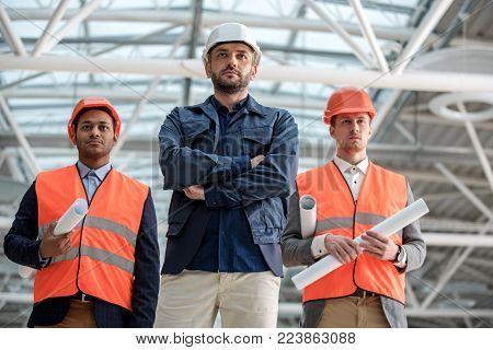 Low angle portrait of serious skillful architects are standing confidently on construction area. They are wearing safety-helmet and holding blueprints