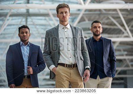 Best team. Portrait of stylish qualified young businessmen are standing together and looking at camera seriously while expressing confidence. Selective focus