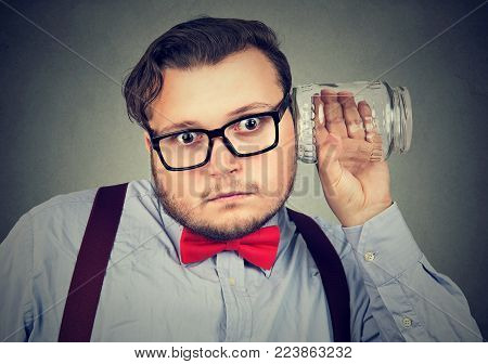 Chubby funny man in glasses holding clear jar next to ear and listening to secrets.