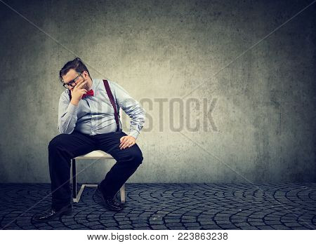 Chubby thoughtful man looking upset and posing in melancholy in chair.