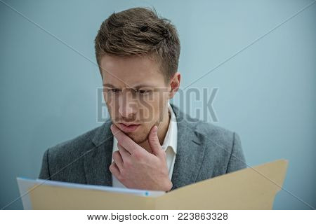 Involved in work. Serious young skilled manager is reading papers with concentration. He is standing thoughtfully while touching his chin