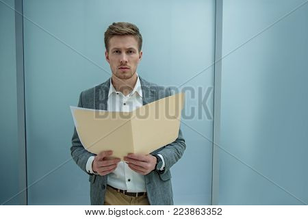 Unsatisfying results. Portrait of serious young businessman is standing with important documents while looking at camera disappointedly. Copy space in the right side