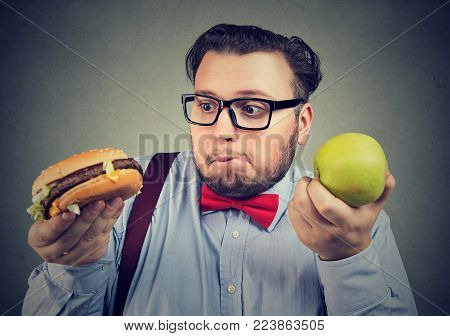 Chubby man in eyeglasses craving delicious burger instead of green apple looking confused.