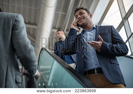 Always in touch. Low angle of elegant man is talking on mobile phone while descending on escalator with other people inside of building. He is looking aside and gesticulating. Selective focus