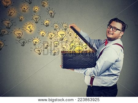 Side view of chunky man holding box with brilliant ideas bein creative and smiling at camera.
