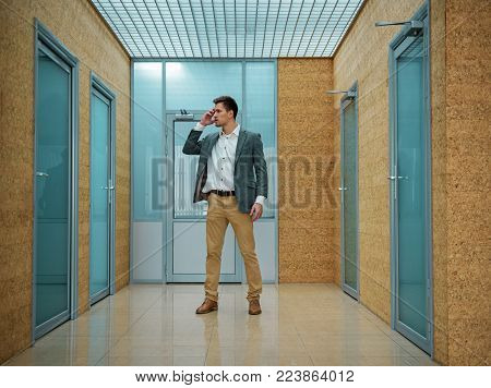 Which way. Full length of confused young man is standing in hallway and looking at door bewildered while trying to find right direction. He is touching his head