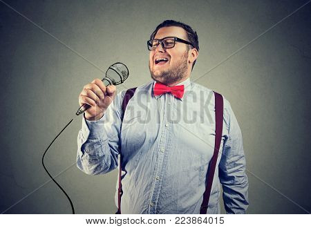 Young chubby man in formal outfit and eyeglasses singing with deep emotions.