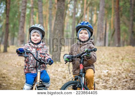 Two Little Boys Riding On Scooter In Summer Park. Smiling And Looking To Each Other. Wear On T-shirt