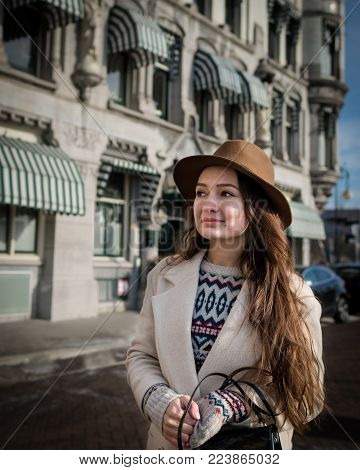 Portrait of a young female tourist with elegant clothes walking in the city. Trendy woman traveler with smile looking on buildings and touring old town. Beautiful girl exploring Rotterdam, Netherlands