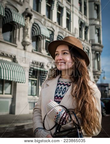 Portrait of a young female tourist with elegant clothes exploring the city. Trendy woman traveler with smile looking on buildings and touring old town. Beautiful girl walks in Rotterdam, Netherlands.