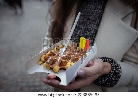 Belgian waffles decorated with the national flag in the young woman hands. Close up view. Hands holds fresh waffles with milk chocolate.