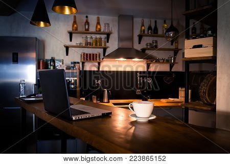 Kitchen with bar counter. Home atmosphere, work in the evening after a hard day with cup of coffee. Home office.
