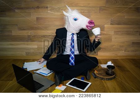 Young man wearing funny mask sits on the floor against a wall and drinks coffee. Unicorn in a suit and tie works in home office on laptop and gadgets on wooden background