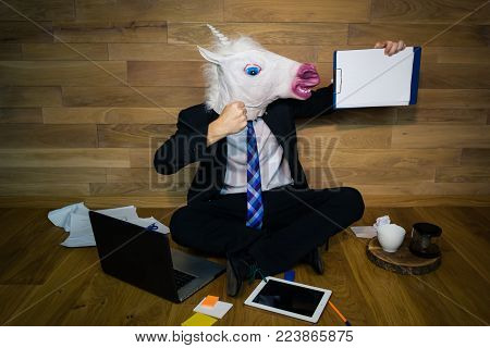 Young man in rubber mask sits on the floor against a wall and works. Unicorn in a suit and tie smiles and shows his power and a white empty sheet with copy space. Any text possible