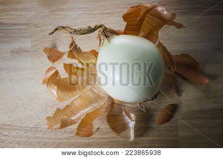Peeled Onion on Wood background with peel