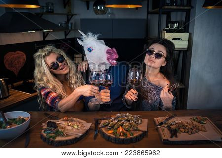Two beautiful women with funny unicorn has dinner together. Group of young people drinks wine and enjoying evening. Man in a funny rubber mask. Crazy party in modern home kitchen at the bar counter