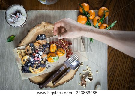 Woman hand decorates dish for breakfast on the stylish wooden tray. Pancakes and parfait decorated with fruits and toppings and nuts on the wooden table. Final touch. Ready to eat. Close up view.