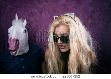 Freaky blonde girl in sunglass and kitty ears with funny guy in horse head mask on the purple background. Fantasy unicorn keep calm with girlfriend. Unusual young people sits together.