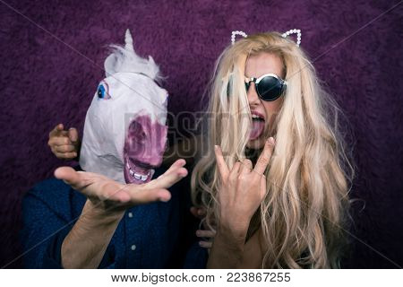 Two funny persons on the purple background shows emotions. Crazy unicorn with expressive young woman. Blonde girl with man from fantasy actively gesticulate