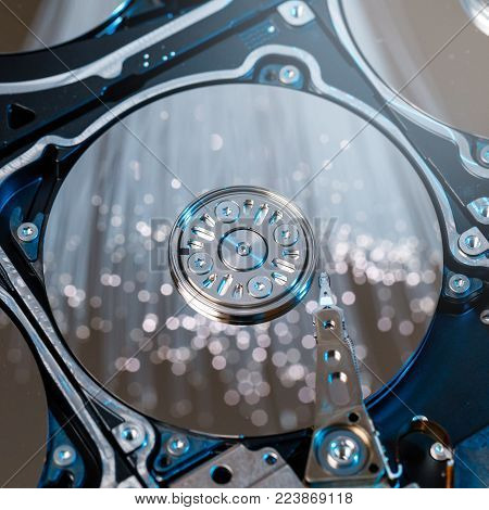 disassembled hard disk, magnetic heads and polished plates illuminated optical fiber with blurred lights.