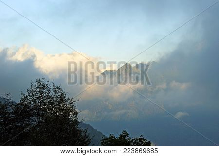 evening view from the mountain slope, which is in the shade, to the sunlit mountain peak among the clouds, located on the other side of the valley