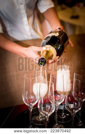Waitress pouring champagne from bottle into a glass. Wedding party in the restaurant at night. Celebration event. Hands close up