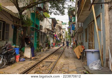 Hanoi, Vietnam - 16th December 2017. A woman checks her washing machine outside her house on a residential street in central Hanoi which has grown up around the north-bound train track
