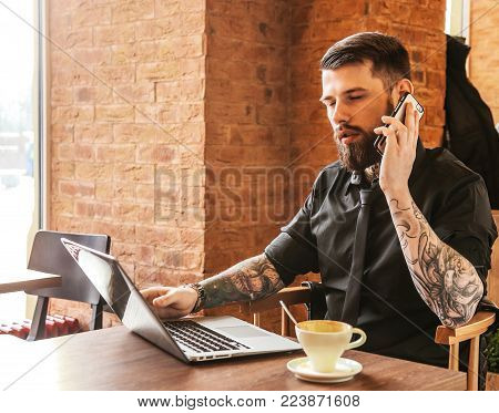 Modern guy calling by smartphone in a caffe