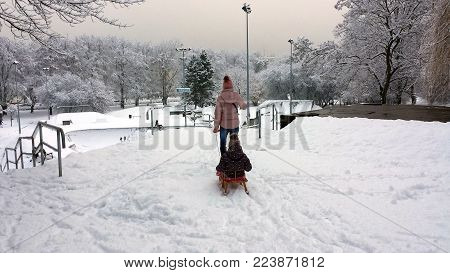 Gdynia, Poland - January 21, 2018:  A woman is pulling a child on a sled. Winter landscape.
