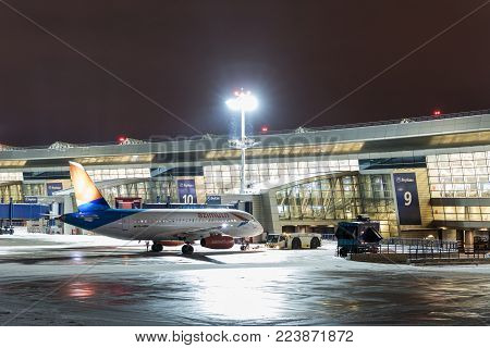 MOSCOW, RUSSIA - 25 december 2017: Night view of Terminal A of Vnukovo International Airport and Sukhoi Superjet of Azimut Airlines.
