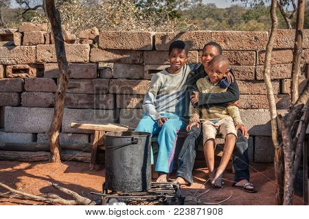 African family sitting inside the outdoors kitchen in the village, Botswana